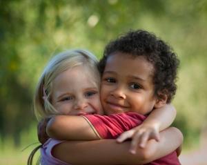 Multi-racial children hug eachother